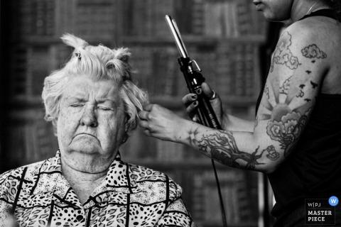 Un miembro de la fiesta nupcial se sienta con los ojos cerrados mientras una peluquera riza su cabello en esta foto en blanco y negro de un fotógrafo de bodas de Nueva Jersey.