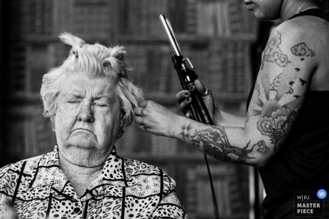 A member of the bridal party sits with her eyes closed while a hairdresser curls her hair in this black and white photo by a New Jersey wedding photographer.