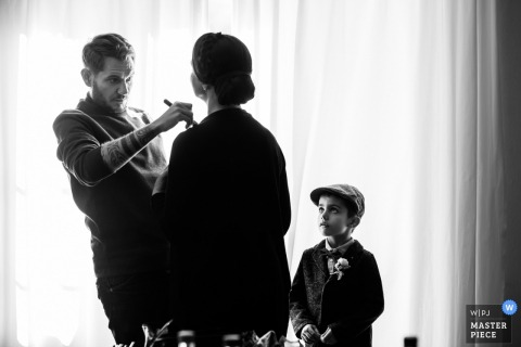 A man helps a woman prepare for the ceremony as a young boy looks on in this black and white photo by a Fribourg, Switzerland wedding photographer.
