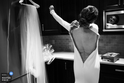 Black and white photo of the bride putting on her dress by a Victoria, British Columbia wedding photographer.
