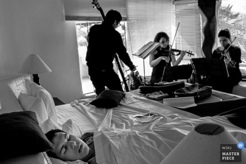 Czarno-białe zdjęcie muzyków przygotowujących się przed ceremonią przez fotografa ślubnego z Limy w Peru.