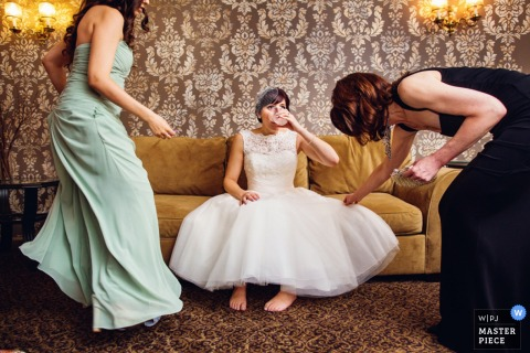 The bride takes a sip of water while her bridesmaids help her prepare in this photo by a New Jersey wedding photographer.