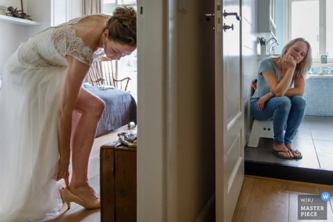 A bride slips her heel on while her companion waits next door in this photo by an Amsterdam, Holland wedding photographer.