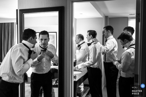 Black and white photo of groomsmen getting ready before the ceremony by a Detroit, MI wedding photographer.