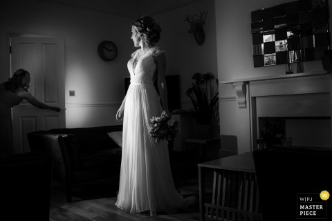 Black and white photo of a bride standing in her dress as a woman is opening the door by a top Devon wedding photographer