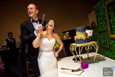 The bride and groom laugh as the grasp a knife preparing to slice their cake in this photo by a San Diego, CA wedding photographer.