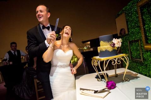 La novia y el novio se ríen mientras agarran un cuchillo que se prepara para cortar su pastel en esta foto de un fotógrafo de bodas de San Diego, California.