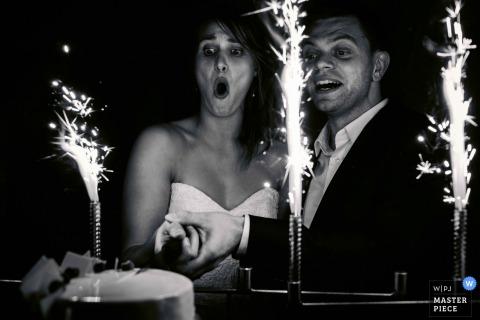 Photo noir et blanc de la mariée et du marié coupant leur gâteau au milieu des feux de Bengale par un photographe de mariage de Flandre orientale, Belgique.