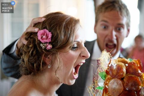 Pan młody udaje, że wepchnął twarz panny młodej w tort weselny na tym zdjęciu przez francuskiego fotografa ślubnego.
