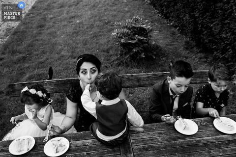 Une femme est assise, en train de manger un gâteau avec des enfants, tandis qu'un jeune garçon la mange sur cette photo en noir et blanc d'un photographe de mariage à Rotterdam.