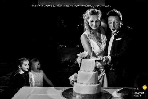 Photo noir et blanc de deux jeunes enfants regardant avec enthousiasme la mariée et le marié couper leur gâteau par un photographe de mariage à Rotterdam.
