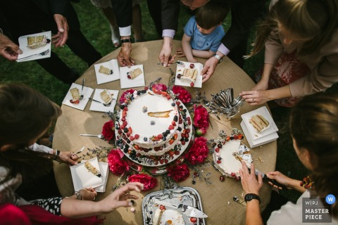Photo of wedding guests waiting to enjoy a slice of cake topped with fruit by a Lower Saxony, Germany wedding photographer.