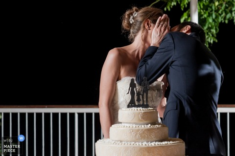 The groom kisses his bride as the two stand in front of their wedding cake in this photo by a Venice wedding photographer.