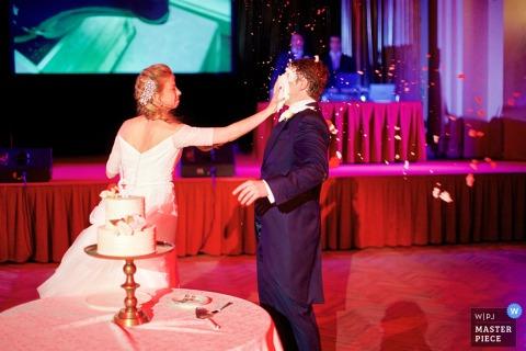 Panna młoda rozmazuje tort weselny na twarzy pana młodego na tym zdjęciu fotografa ślubnego z Europy.