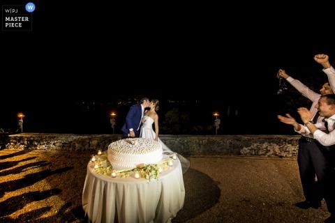De bruid en bruidegom kussen voor hun bruidstaart terwijl hun gasten juichen op deze foto door een huwelijksfotograaf uit Lombardije, Italië.