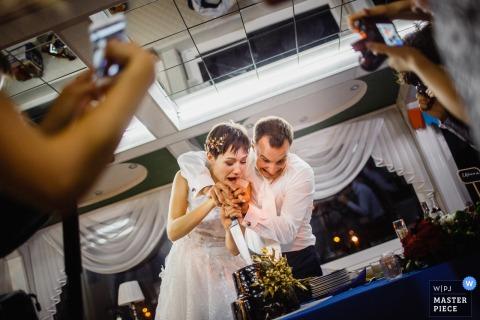 Gasten maken foto's van de bruid en bruidegom als de eerste plak in hun cake op deze foto door een Russische huwelijksfotograaf.