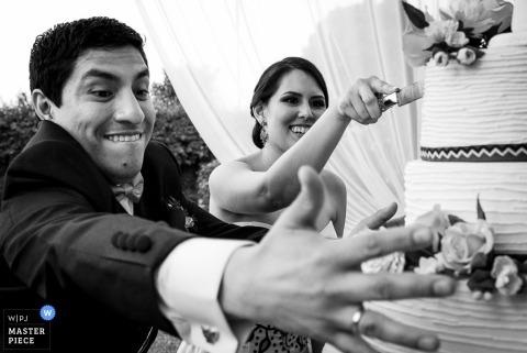 Czarno-białe zdjęcie nowożeńców, gdy panna młoda robi pierwszy kawałek ciasta przez fotografa ślubnego z Limy w Peru.