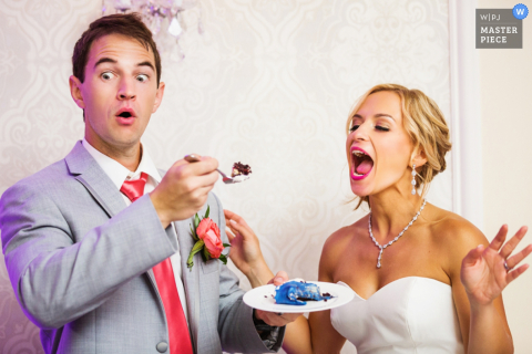 The bride waits with her mouth open while her groom prepares to feed her a bite of cake in this photo by a New Jersey wedding photographer.