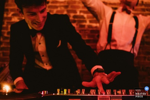 Photo of a man adjusting a DJ mixer by a North Yorkshire, England wedding reportage photographer.