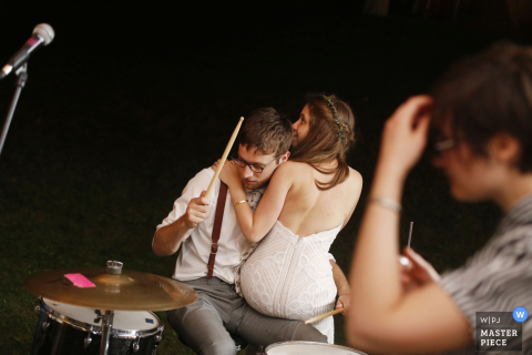 The bride sits on the drummer's lap in this photo by a Tunbridge, VT wedding photographer.
