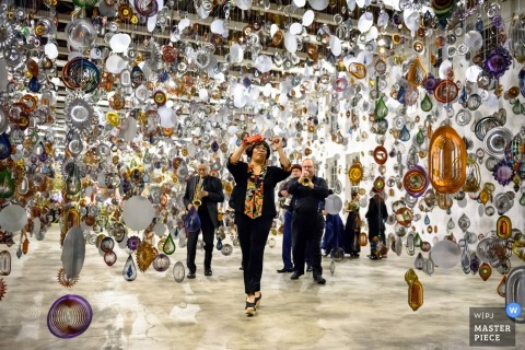 Musicians play in a room filled with shining mobiles hanging from the ceiling in this photo by a New York wedding photographer.