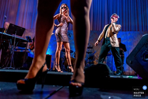 Through legs on the dance floor, San Diego wedding photographer captured this photo of the wedding band performing