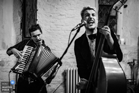 Black and white photo of the bassist and accordionist playing during the reception by a West Yorkshire, England wedding reportage photographer.