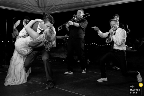 The groom dips his bride and kisses her on the dance floor in front of the band in this black and white photo by a Carson City, NV wedding photographer.