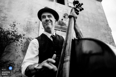 Black and white photo of a man playing the bass by a France wedding photographer.