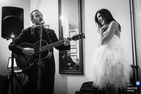 The bride is serenaded by a man singing and playing guitar in this black and white photo by a Calabria wedding photographer.