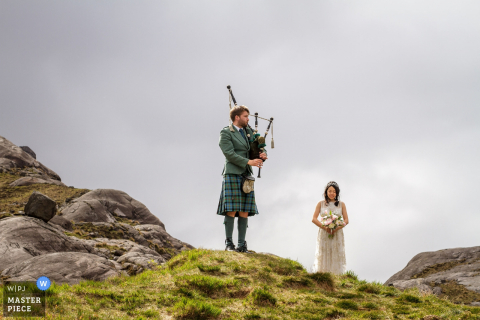 The bride stands on a hill as a man plays the bagpipes in this photo by a Scotland wedding reportage photographer.