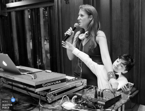 Black and white photo of a young boy attempting to take the microphone from the DJ by a Chicago, IL wedding photographer.