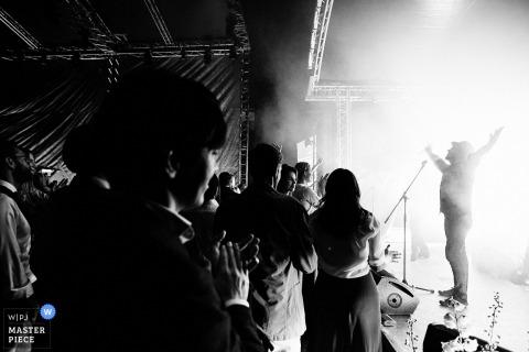 Zwart-witte foto van de gasten die een uitvoerder op stadium toejuichen door een huwelijksfotograaf van Sint-Petersburg, Rusland.