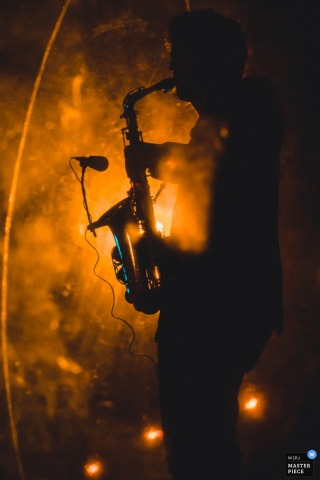 Vertical image of a sax player silhouetted by orange DJ lights and fog by a top Paris wedding photographer.