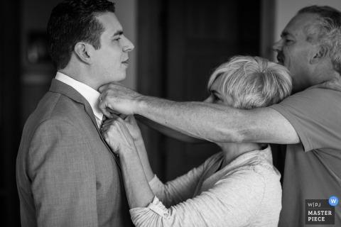Rodzice pana młodego pomagają mu w krawacie w tym czarno-białym zdjęciu autorstwa fotografa ślubnego Missoula, MT.