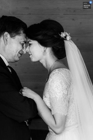 Foto en blanco y negro de la novia y su padre tocando la frente por un fotógrafo de bodas en Praga.