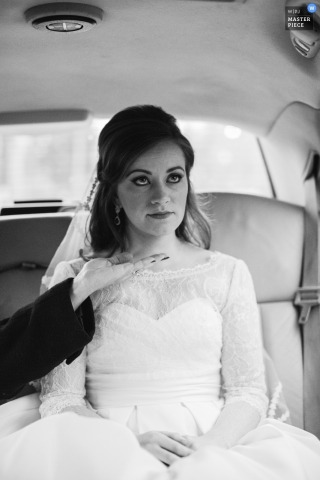 This black and white bridal image of a bride riding in a car on the way to her ceremony was captured by a Saratoga Springs wedding photographer