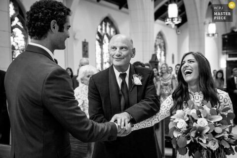 Le père de la mariée donne la main au marié sur cette photo en noir et blanc réalisée par un photographe de mariage du New Jersey.