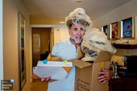 This gentleman is overloaded with responsibilites and reception party hats in this image by a Key West, FL wedding photographer.