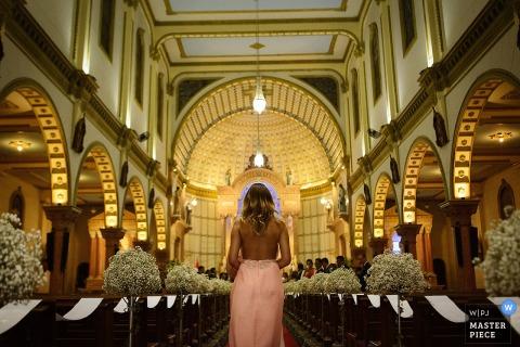 Fotograf ślubny w Limie stworzył to zdjęcie druhny idącej wzdłuż nawy kościoła wyłożonej białymi kwiatami