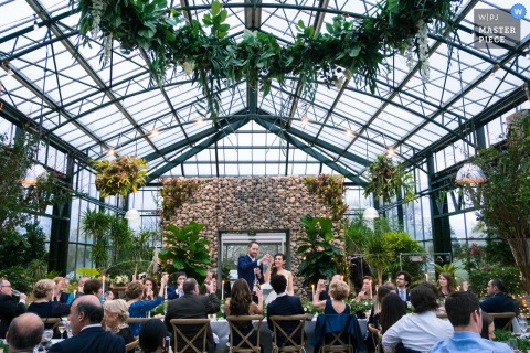 Detroit wedding photographer created this image of a foliage filled wedding ceremony in a greenhouse