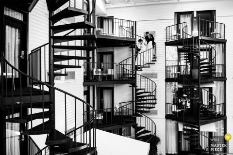 Detroit-Hochzeitsfotograf nahm dieses Schwarzweiss-Bild einer Braut und des Bräutigams gefangen, die hinunter eine Wendeltreppe gehen