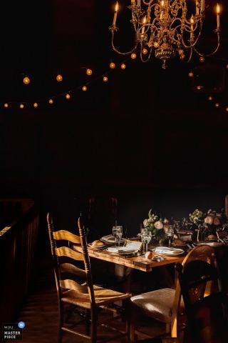 Esta foto nocturna de una mesa de banquete colocada bajo una brillante lámpara de araña y luces de cadena que esperan a los invitados a la boda fue tomada por un fotógrafo de bodas de Nueva Jersey.