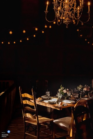 This night time shot of a banquet table set under a glowing chandelier and string lights waiting for the wedding guests to arrive was taken by a top New Jersey wedding photographer