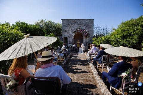 Lecce Hochzeitsfotograf erstellt dieses Bild von einer Outdoor-Zeremonie an einem sonnigen Tag, während die Gäste unter Sonnenschirmen beobachten