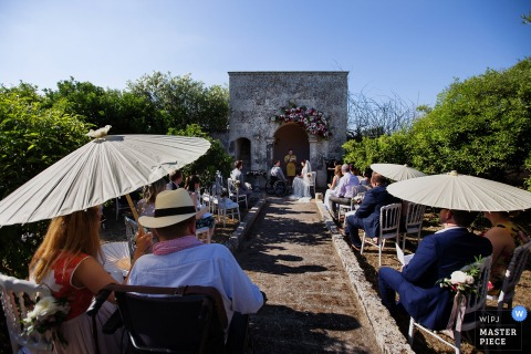 Lecce wedding photographer created this picture of an outdoor ceremony on a sunny day, while guests watch under parasols