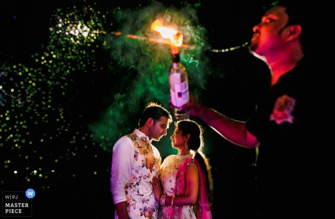 India wedding photographer captured this image of a bride and groom gazing lovingly at each other while a fire breather performs in the foreground