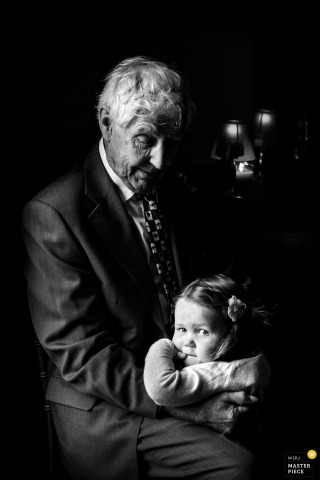 West Yorkshire wedding photographer captured this black and white portrait of a little girl being held by her grandfather