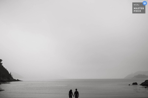 Hong Kong wedding photographer captured this black and white image of a bride and groom standing in front of a body of water while fog rolls in
