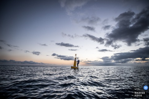 This distance shot of a bride and groom standing on a buoy in the ocean at sun set was captured by a Miami wedding photographer